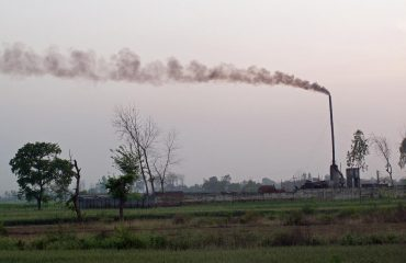 spewing smoke and .pollution into a green rural environment